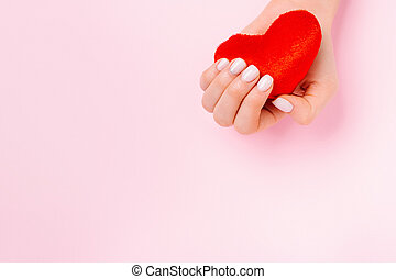 A tender female hand holds a soft red heart on a pink background with blank advertising space.