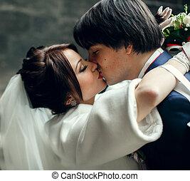 A tender kiss of beautiful newlyweds