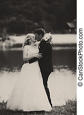 A tender kiss of newlyweds standing on the lake shore