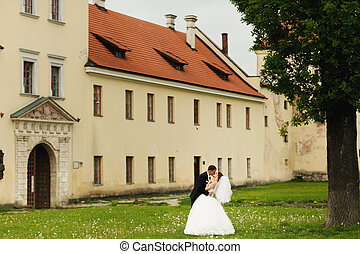 A tender kiss of newlyweds while walking around
