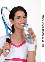A tennis woman having a sip of water.