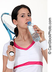 A tennis woman taking a sip of water.