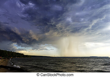 A terrible blue cloud with a heavy rainfall over the sea.