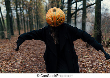 A terrible creature in the autumn forest in the evening. Happy Halloween. Pumpkin head. Man with a pumpkin on his head and a black cloak
