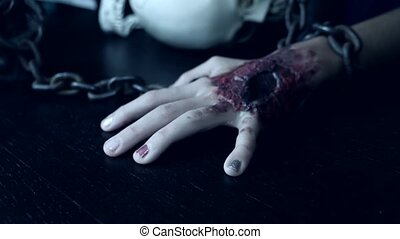 A terrible hand with a bloody wound is chained to an iron...