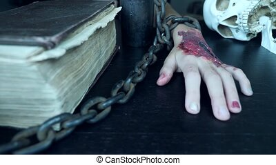 A terrible hand with a bloody wound is chained to an iron chain. hand monster on halloween. 4k, slow motion