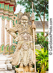 a terrible stone guard is located near the temple in Bangkok
