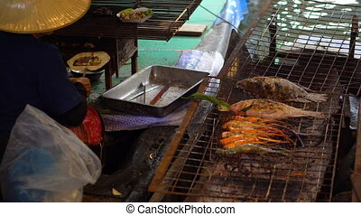 A Thai Woman in Traditional Cloth Cooking Big Shrimps on a Barbecue Fire in the Boat at Floating Market, Bangkok.