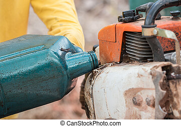 Thai worker filling oil to engine of chainsaw