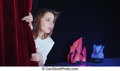 A theater stage. A girl looking out of the backstage cloth,...