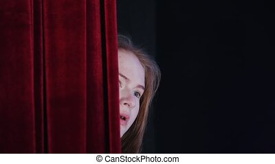 A theater stage. A scared girl looking out of the backstage...