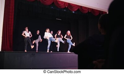 A theater stage. People on the stage performing a group dance