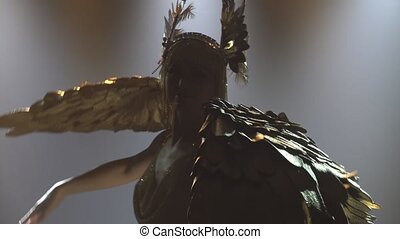 A theatrical performance featuring the Greek goddess Artemis. Charming woman in a golden costume with wings dances and sings in a dark studio with backlight. Silhouette. Close up