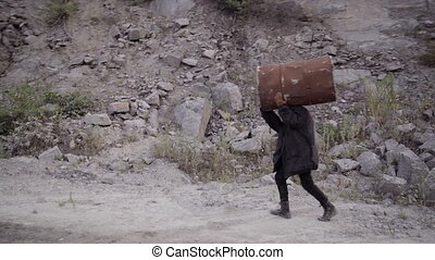 A thief, a criminal carries a stolen barrel in quarry