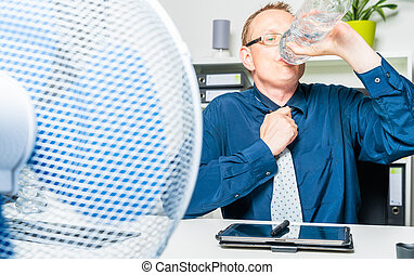 thirsty businessman works in the office on a hot day and sweats