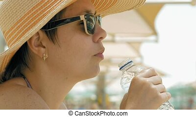 A thirsty female is drinking water at the beach - A female...