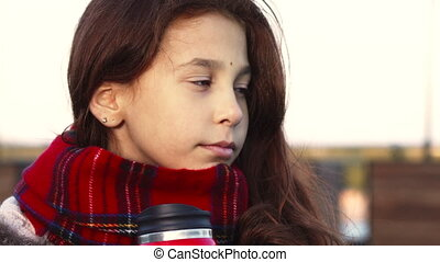 A thoughtful girl drinks a warm drink from a hot mug