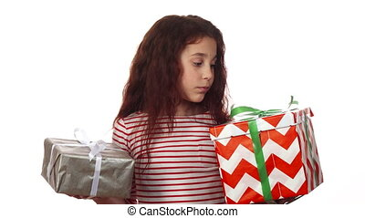 A thoughtful girl looks at her two gifts and chooses among them