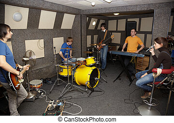 a thoughtful rock band. sad vocalist girl, two musicians with electro guitars and one drummer working in studio.