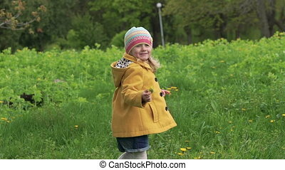 A three years old girl playing and holding flowers in a park. Slowly