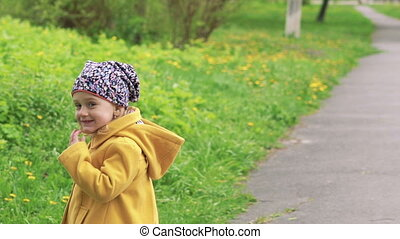 A three years old girl walking in the park. Slowly