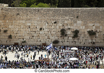 A Thursday morning at the Western Wall, one of the most sacred places to the Jewish religion. The place is filled with Bar-Mitzvah boys and their families, practicing the ceremony of putting on phyla