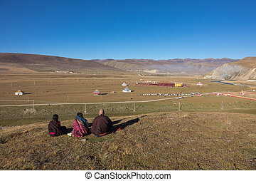 A Tibetan monks sitting on the hill at sunlight in Yarchen Gar, Sichuan, China. Yarchen Gar is the largest concentration of nuns and monks in the world.