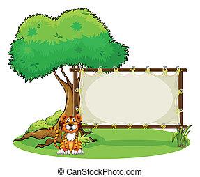 A tiger beside a rectangular signage