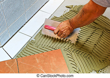 tiler at work - a tiler at work. sticking floor tiles with...