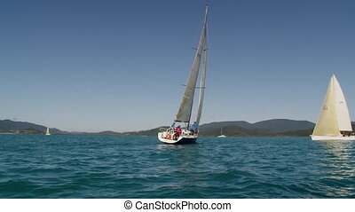 A tilted sailboat on the blue ocean