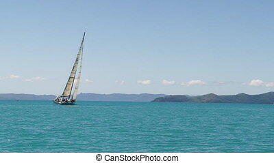 A long shot of a small sailboat that is tilted while sailing the great blue sea. The shot is taken in slow motion.