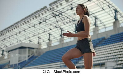A time lapse portrait of beautiful woman running on the stadium bleachers with concentrated deep breathing and motivating myself and consciousness for the race. Discard unnecessary emotions and tune in to win, preparing for the race