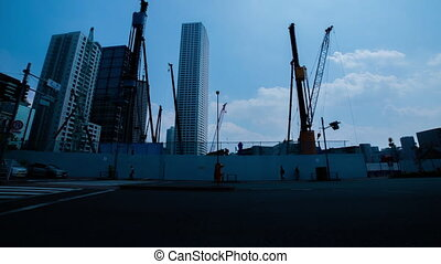 A timelapse of moving cranes at the under construction in Tokyo wide shot zoom