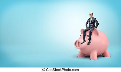 A tiny businessman calmly sits on a giant piggy bank's head on blue background.