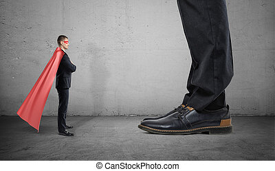 A tiny businessman in a superhero cape stands facing giant man with only his feet seen.