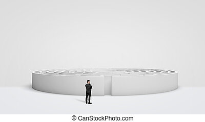 A tiny businessman standing in front of a large white round maze right next to the entrance.