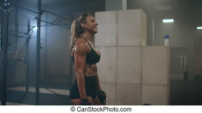 A tired, happy woman in the gym, her body glistening with sweat, is laughing and smiling after a hard workout. the pleasure of sports. High quality 4k footage
