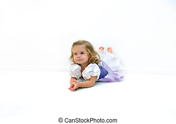 A tired little ballerina lays on the floor in an all white room. She is dressed in a ballerina costume of lilac and purple. She has an enduring expression on her face.