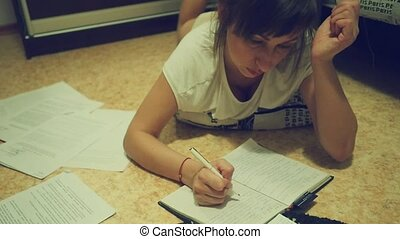 A tired young woman doing homework for university at night