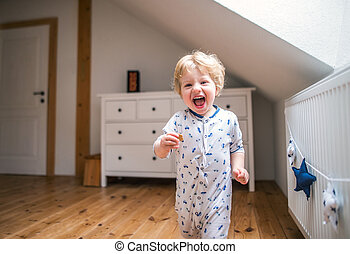 A toddler boy in the bedroom at home.