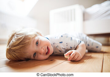 A toddler boy on the floor in the bedroom at home.