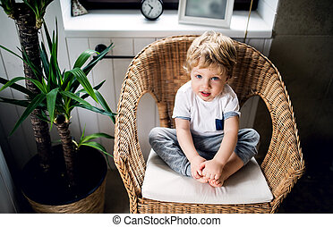 A toddler boy sitting on the wicker chair in the bathroom at home.