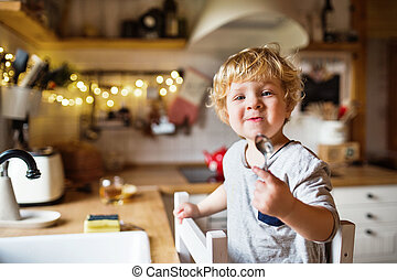 A toddler boy washing up the dishes. - A cute toddler boy...