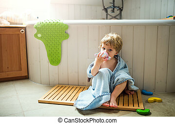 A toddler boy wrapped in towel sitting on the floor in the bathroom at home.