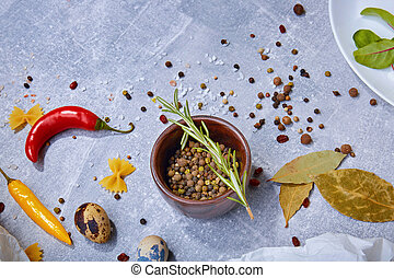 A top view of a brown wooden bowl with seasoning on a gray background. Spices with hot pepper, bay leaves and a rosemary twig.