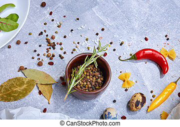 A top view of a brown wooden bowl with seasoning on a gray background. Spices with hot peppers, bay leaves and a rosemary twig.