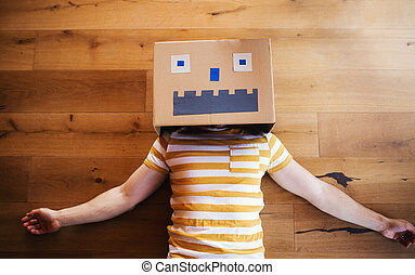 A top view of man with cardboard monster on head lying down indoors at home.
