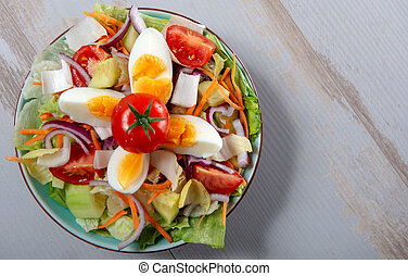 top view of plate of vegetable salad on wooden table