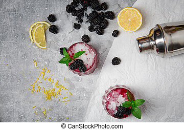 A top view of two refreshing cocktails with blackberries and green mint on a gray background. Organic and natural berries and yellow lemon.