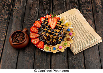 a top view pancakes with fruits on the brown desk